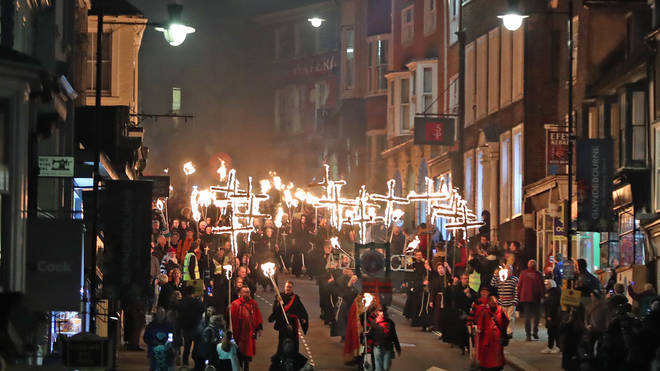 People in Lewes, east Sussex, make their way through the procession