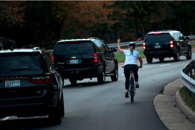 Juli Briskman gestures with her middle finger as a motorcade with US President Donald Trump departs Trump National Golf Course