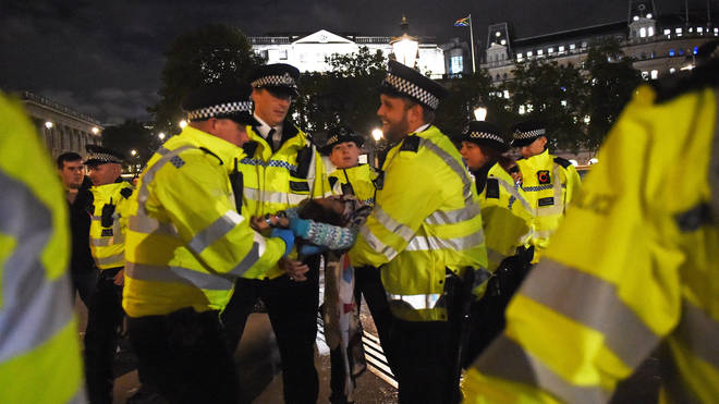 An activist being removed from Trafalgar Square by police