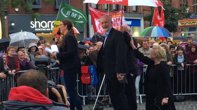Jeremy Corbyn laughs as he stays dry under an umbrella