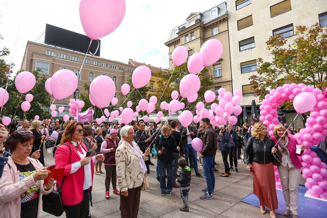 People hold pink balloons during breast cancer campaigning in Croatia