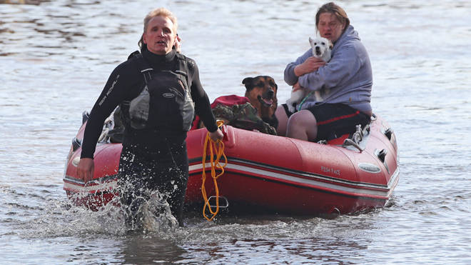A flood victim is taken to safety with two dogs in Doncaster