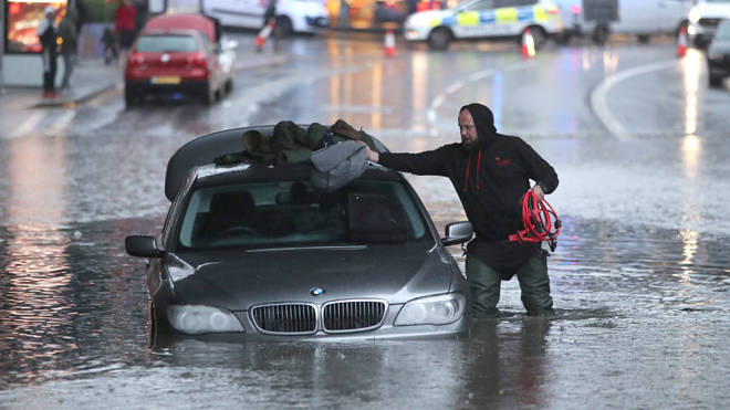 A man retrieves his belongings from his stranded car in Sheffield