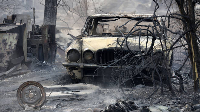 The burnt out shell of a Jaguar vehicle sits in the ruins of a smouldering house in New South Wales