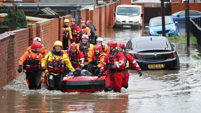 Fire and Rescue service members pull an inflatable boat that has been used to rescue residents trapped by floodwater in Doncaster