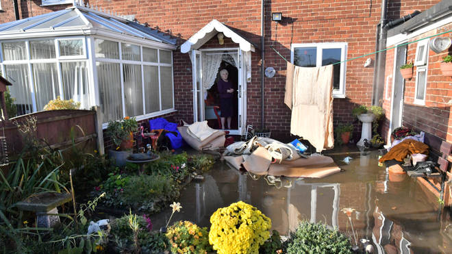 Dossie Croucher standing at her backdoor looking at her flooded garden in Fishlake, Doncaster