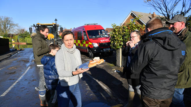 Helen Edwards hands out free bacon sandwiches to villagers in Fishlake, Doncaster as parts of England endured a month's worth of rain in 24 hours.