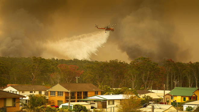 A helicopter drops water on fires in an attempt to save houses