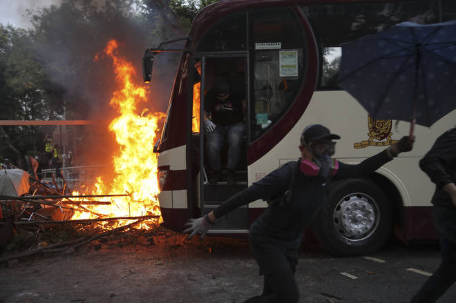 Students run past fire set near a bus during a face-off with riot police at the Chinese University in Hong Kong