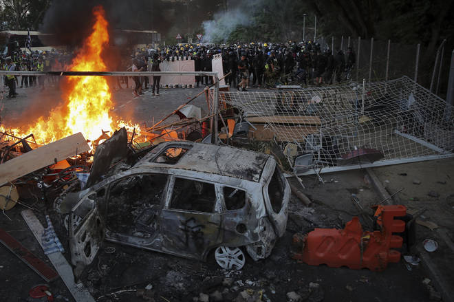 Students stand near a fire and a charred vehicle during a face-off with riot police