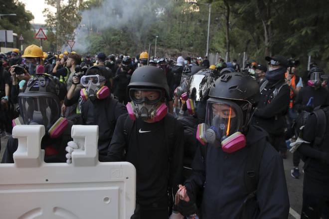 Students with gas masks stand watch behind barricades after a faced-off with riot police at the Chinese University in Hong Kong