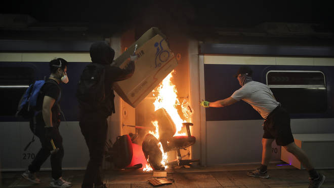 Students burn a train inside the Chinese University MTR station