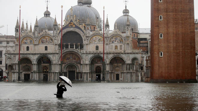 A member of the public wades through water outside St Mark's Basilica