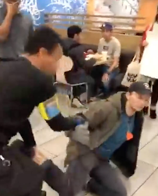At one point a protester is dragged by his foot