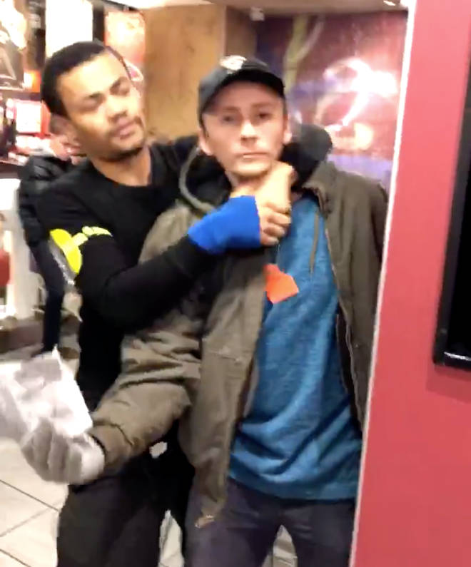 The security guard gets one activist in a headlock
