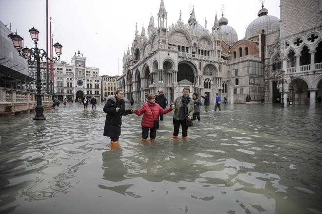 People wade through water in a flooded St. Mark's Square in Venice
