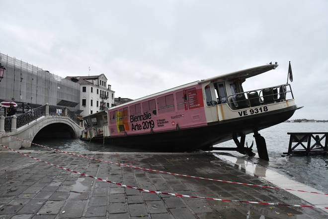 A stranded ferry boat lies on its side in Venice