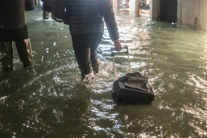 A tourist walks near a store after the exceptional high tide or 'Alta Acqua' that reached 190 cm at late night