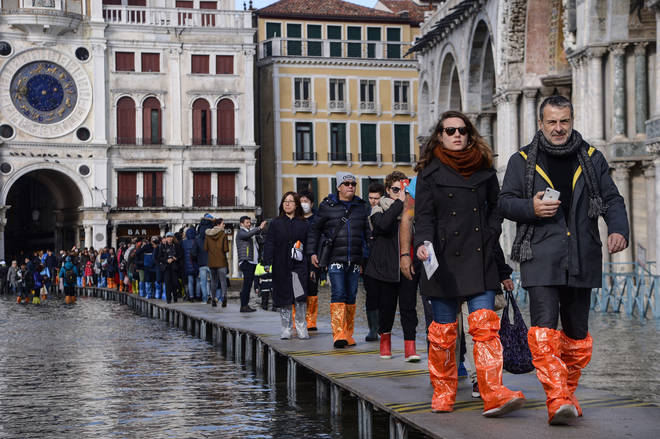People in wellies walk on a footbridge across the flooded St. Mark's Square