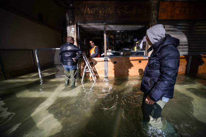 A man walks past a cafe across a flooded arcade by St. Mark's Square