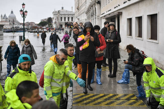 Volunteers set up a footbridge for pedestrians across the flooded Riva degli Schiavoni embankment
