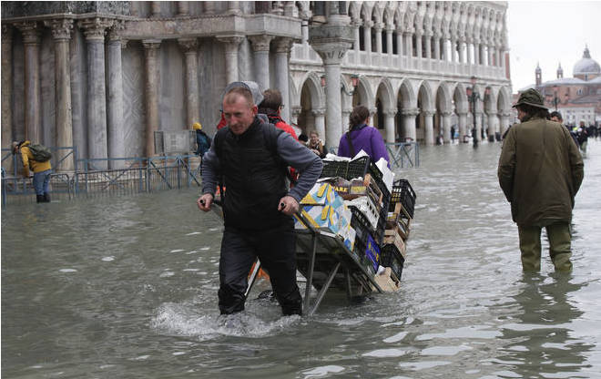 A greengrocer pulls his cart through high water in Venice