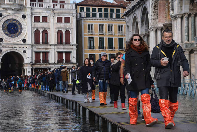 People in wellies walk on a footbridge across the flooded St. Mark's Square.
