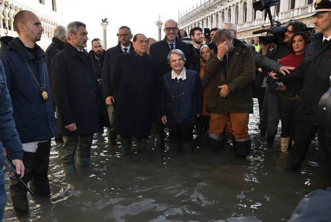 Former Italian Premier Silvio Berlusconi, center left in a flooded St. Mark's Square in Venice.