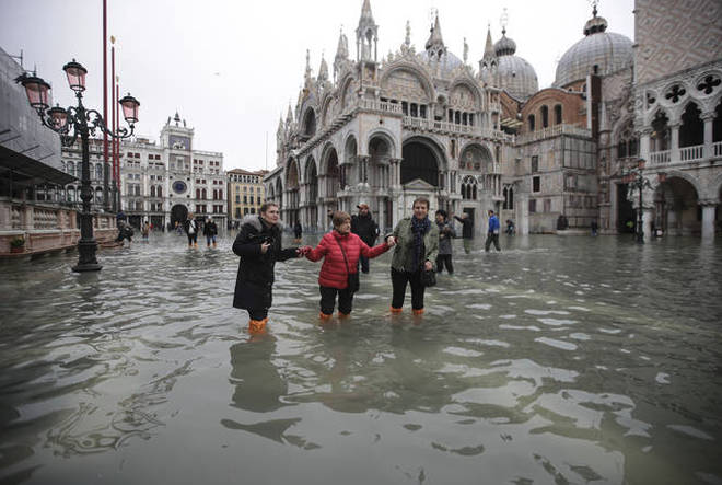 People wade through water in a flooded St. Mark's Square in Venice.