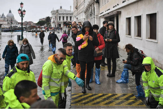 Volunteers set up a footbridge for pedestrians across the flooded Riva degli Schiavoni embankment.