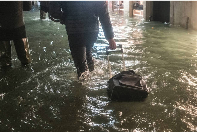 A tourist walks near a store after the exceptional high tide or 'Alta Acqua' that reached 190 cm at late night.