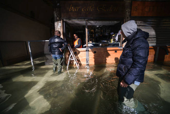 A man walks past a cafe across a flooded arcade by St. Mark's Square.
