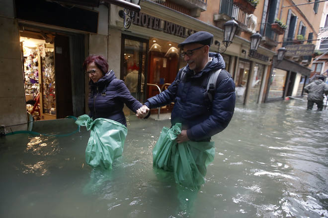A couple wades their way through water in Venice