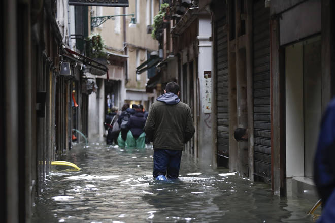 People wade their way through flooded streets in Venice