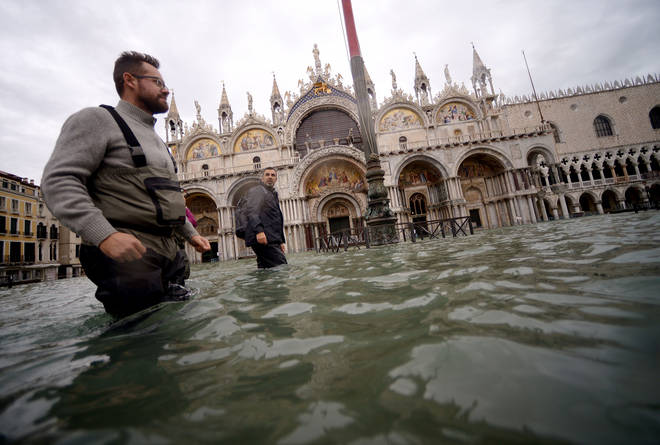 A man wearing waterproof fishing waders walks across the flooded St. Mark's Square