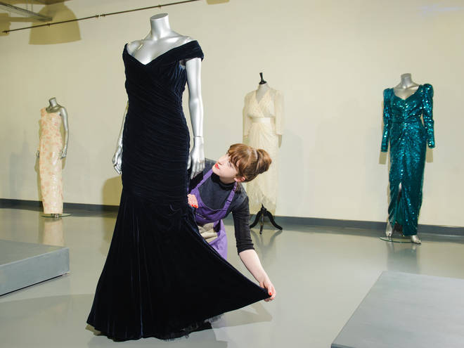 House assistant Lucy Bishop adjusts a midnight-blue velvet Victor Edelstein evening gown, at Kerry Taylor Auctions