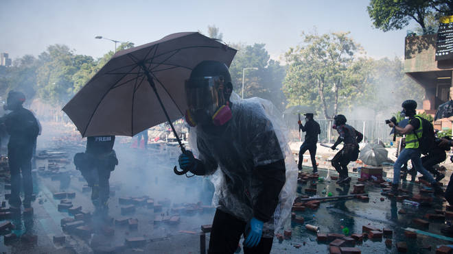 Protesters use umbrellas to shield themselves