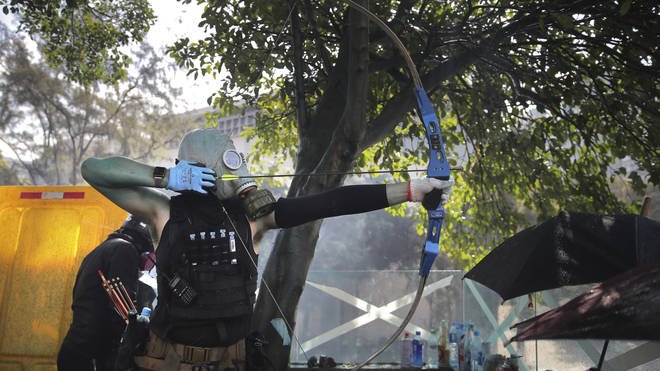 A protester with a bow prepares to fire
