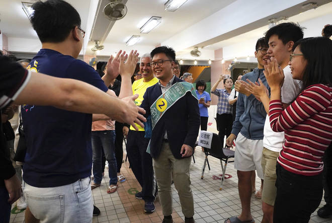 Pro-democracy candidate James Yu, center, celebrates with supporters after winning his seat in district council elections in Hong Kong.