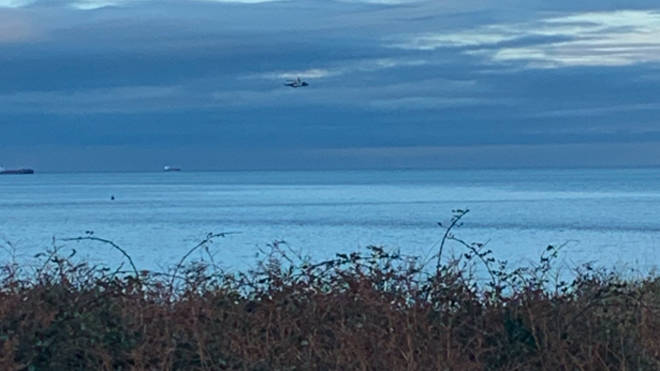 A coastguard helicopter searches for the plane off the coast of Anglesey