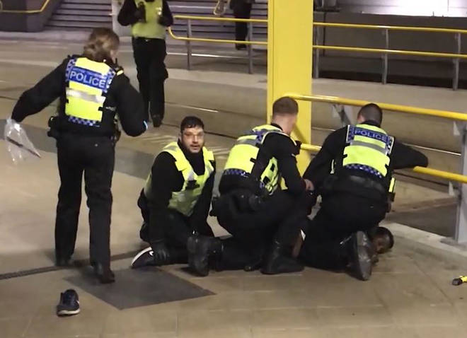 Police restraining a man after he stabbed three people at Victoria Station in Manchester.